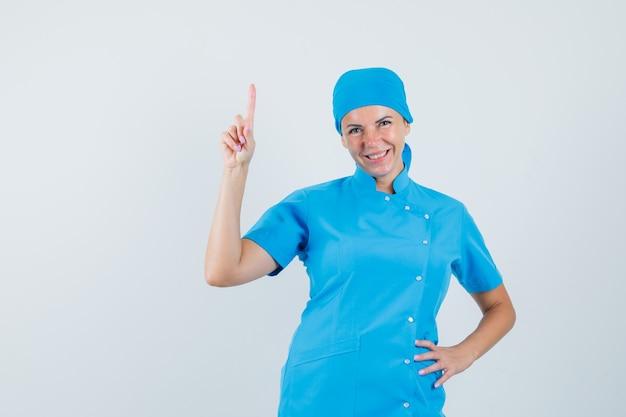 Kobieta lekarz skierowaną w górę w niebieskim mundurze i patrząc wesoły, widok z przodu.