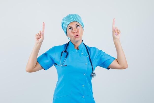 Kobieta lekarz skierowaną w górę w niebieskim mundurze i patrząc z nadzieją. przedni widok.