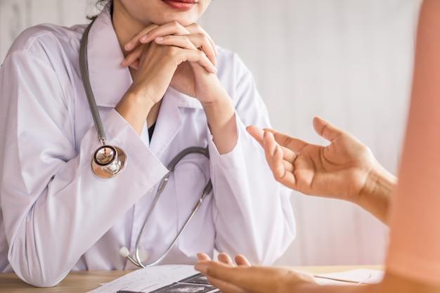 Kobieta lekarz słuchania i rozmowy z pacjentem w szpitalu