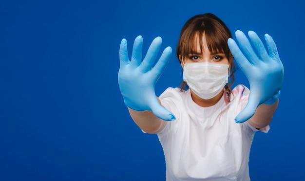 Kobieta lekarz stoi w masce medycznej z rękami w rękawiczkach wyciągniętymi przed sobą na niebieskiej ścianie