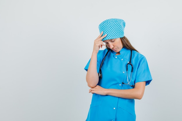 Kobieta lekarz stojący ręką na głowie w niebieskim mundurze i wyglądający na zmęczonego. przedni widok.