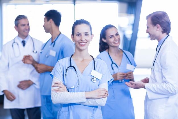 Kobieta lekarz stojący z przodu i uśmiechnięty, podczas gdy jej koledzy dyskusji