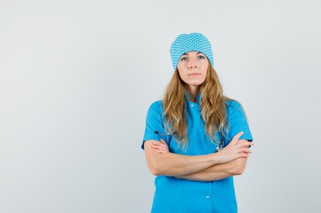 Kobieta lekarz stojący ze skrzyżowanymi rękami w niebieskim mundurze i patrząc poważnie.