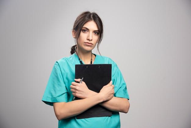 Kobieta lekarz szczelnie trzymając schowek