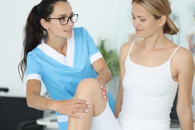 Kobieta lekarz traumatolog w niebieskim garniturze trzyma młodego pacjenta przez kolano w portrecie gabinetu kliniki