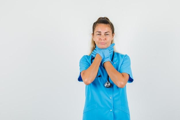 Kobieta lekarz trzyma jej zapalenie gardła w niebieskim mundurze, rękawiczkach i wygląda bolesnie