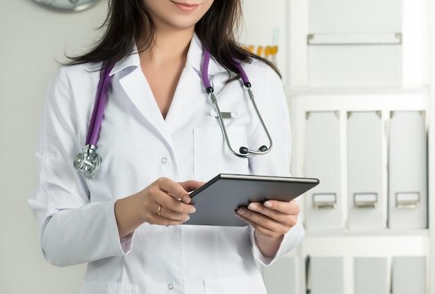 Kobieta lekarz trzyma tablet pc. zbliżenie dłoni lekarza. usługi medyczne i koncepcja opieki zdrowotnej.