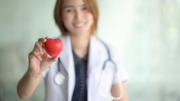 Kobieta lekarz trzymać czerwone serce w szpitalu