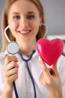 Kobieta lekarz trzymać w ramiona czerwone serce i fonendoskop