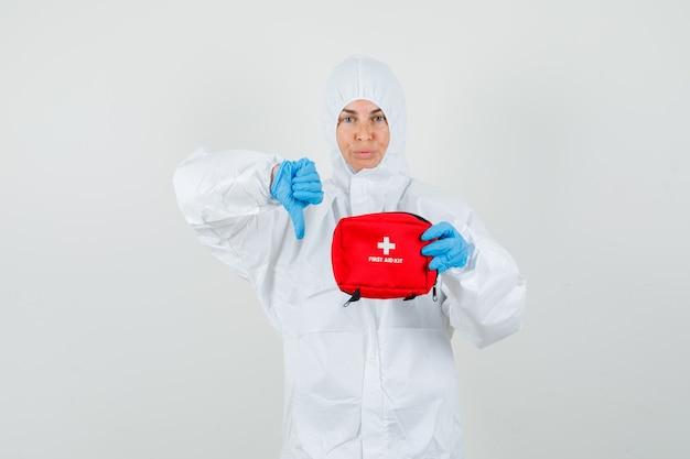 Kobieta lekarz trzymając apteczkę i pokazując kciuk w dół w kombinezonie ochronnym