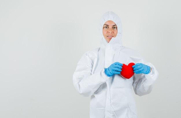 Kobieta lekarz trzymając czerwone serce w kombinezonie ochronnym