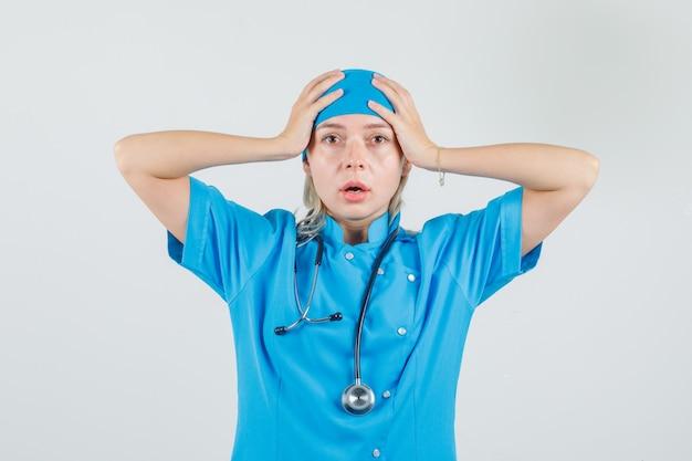 Kobieta lekarz trzymając głowę rękami w niebieskim mundurze i patrząc zdezorientowany