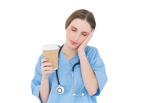 Kobieta lekarz trzymając kubek kawy i podnosząc rękę do jej twarzy z zamkniętymi oczami