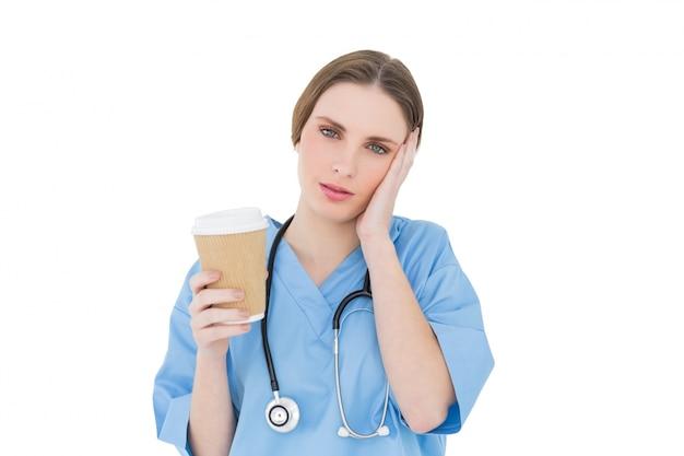 Kobieta lekarz trzymając kubek kawy i podnosząc rękę do jej twarzy