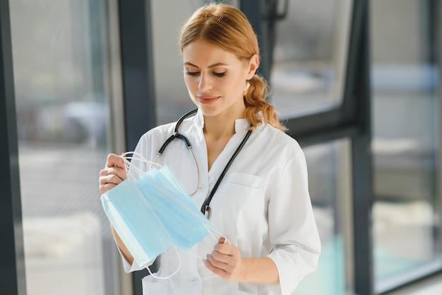 Kobieta lekarz trzymając maski ochronne