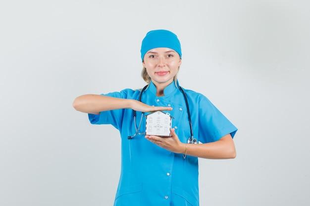 Kobieta lekarz trzymając model domu i uśmiechając się w niebieskim mundurze