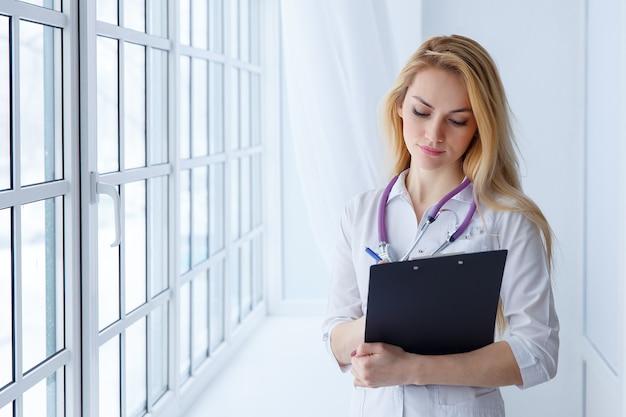 Kobieta lekarz trzymając pióro do pisania w schowku do leczenia pacjenta, koncepcja zdrowego stylu życia