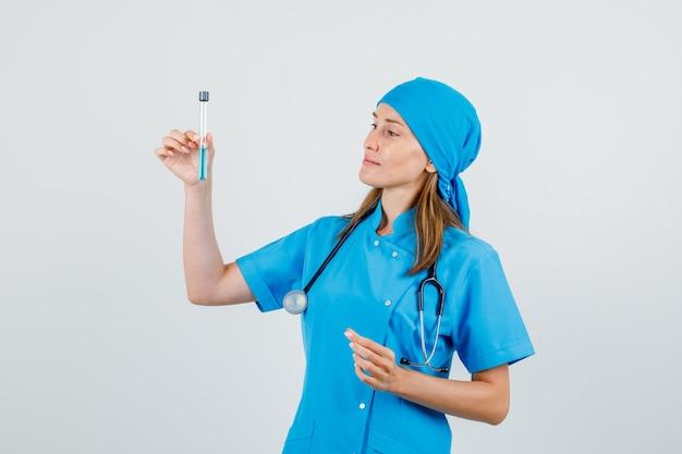 Kobieta lekarz trzymając probówkę i uśmiechając się w jednolity widok z przodu.