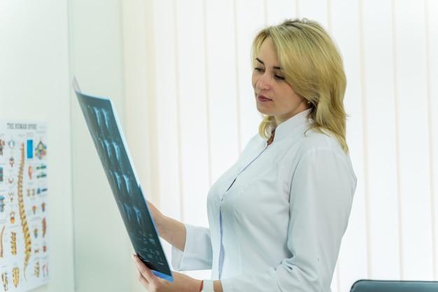 Kobieta lekarz trzymając rtg w nowoczesnej sali medycznej z tomografią komputerową.