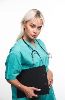 Kobieta lekarz trzymając schowek na białej powierzchni, patrząc poważnie