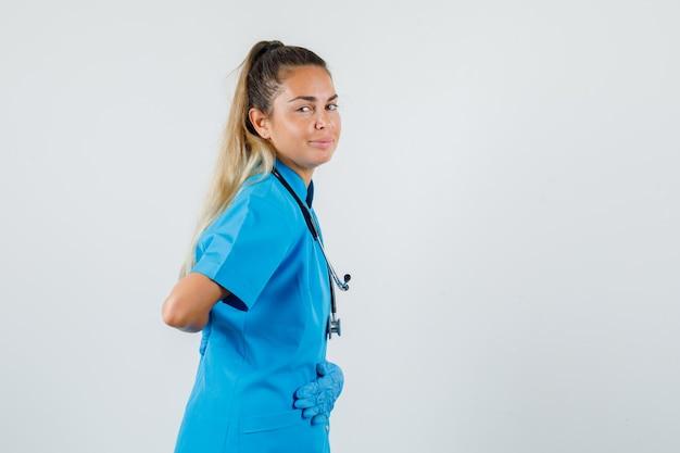 Kobieta lekarz trzymając się za ręce na brzuchu iz powrotem w niebieskim mundurze