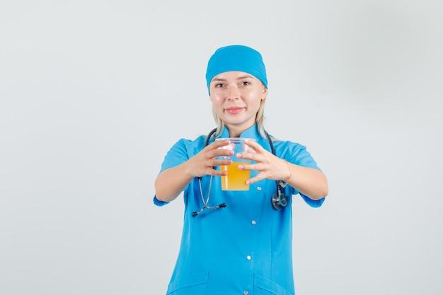 Kobieta lekarz trzymając sok owocowy i uśmiechając się w niebieskim mundurze