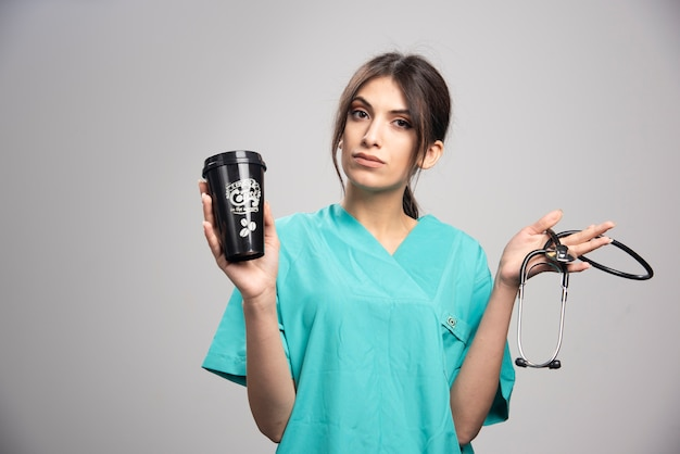 Kobieta lekarz trzymając stetoskop i filiżankę kawy