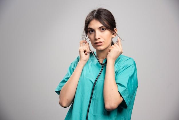 Kobieta lekarz trzymając stetoskop na szaro