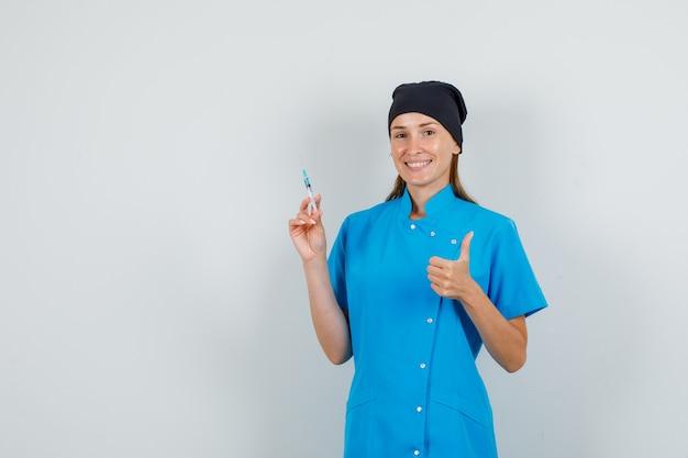 Kobieta lekarz trzymając strzykawkę z kciukiem do góry w niebieskim mundurze, czarnym kapeluszu i patrząc wesoło. przedni widok.
