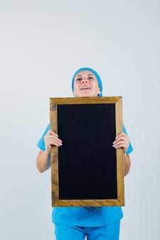Kobieta lekarz trzymając tablicę w niebieskim mundurze i wyglądający wesoło. przedni widok.