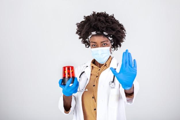 Kobieta lekarz trzymająca syrenę migacza i pokazująca ręką znak stopu przed koronawirusem