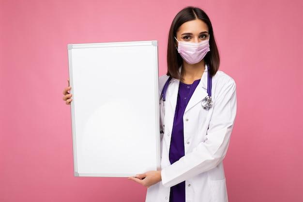Kobieta lekarz ubrana w biały fartuch medyczny i maskę trzyma pustą tablicę
