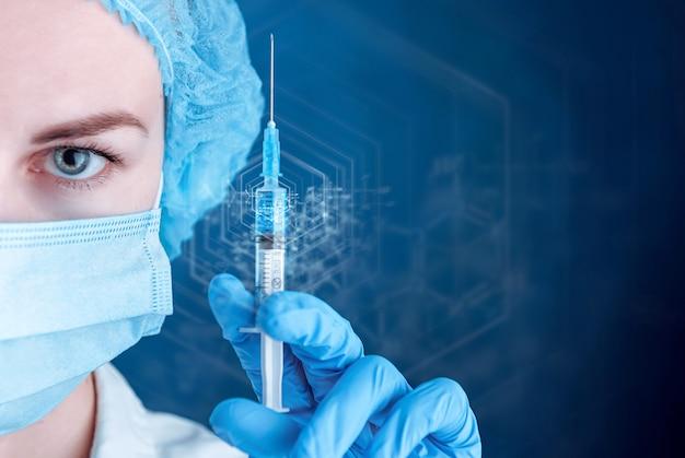 Kobieta lekarz ubrana w maskę trzyma strzykawkę ze szczepionką