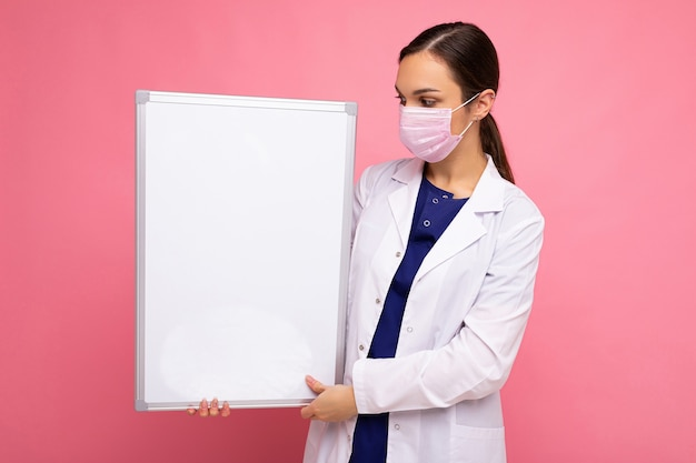Kobieta lekarz ubrany w biały fartuch medyczny i maskę trzymając pustą tablicę z miejscem na kopię tekstu na białym tle. koncepcja koronawirusa.