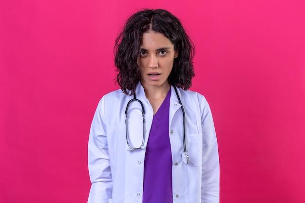 Kobieta lekarz ubrany w biały fartuch ze stetoskopem stojąc z otwartymi ustami patrząc zszokowany na odizolowanej pomarańczy