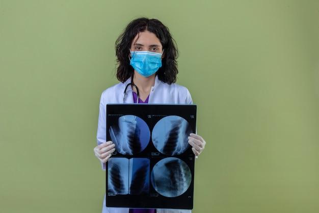 Kobieta lekarz ubrany w biały fartuch ze stetoskopem w medycznej masce ochronnej stojącej z prześwietleniem płuc z poważną twarzą na odizolowanej zieleni