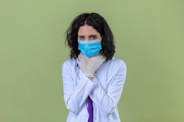 Kobieta lekarz ubrany w biały fartuch ze stetoskopem w medycznej masce ochronnej trzyma ręce na szyi z powodu bólu gardła na odosobnionym zielonym