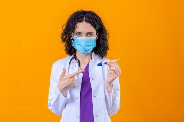 Kobieta lekarz ubrany w biały fartuch ze stetoskopem w medycznej masce ochronnej, wskazując palcem na cyfrowy termometr w rękach z poważną twarzą stojącą