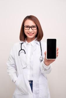 Kobieta lekarz uśmiecha się i pokazuje pusty ekran inteligentny telefon na białym tle