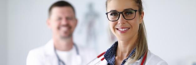 Kobieta lekarz uśmiechając się i trzymając schowek od tyłu jej kolega stoi
