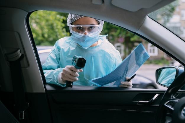 Kobieta lekarz używa pistoletu termometr na czoło na podczerwień, aby sprawdzić temperaturę ciała. w przypadku objawów wirusa covid-19. kobieta w fartuchu izolacyjnym lub kombinezonach ochronnych i chirurgicznych maskach na twarz na zewnątrz.