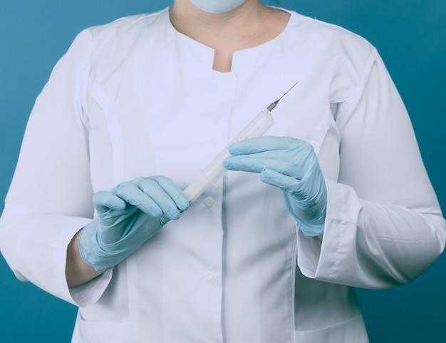 Kobieta lekarz w białym fartuchu i masce stoi na niebieskim tle i trzyma plastikową strzykawkę, poczęcie szczepień
