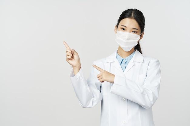 Kobieta lekarz w białym fartuchu medyczna maska kopiuje przestrzeń na białym tle