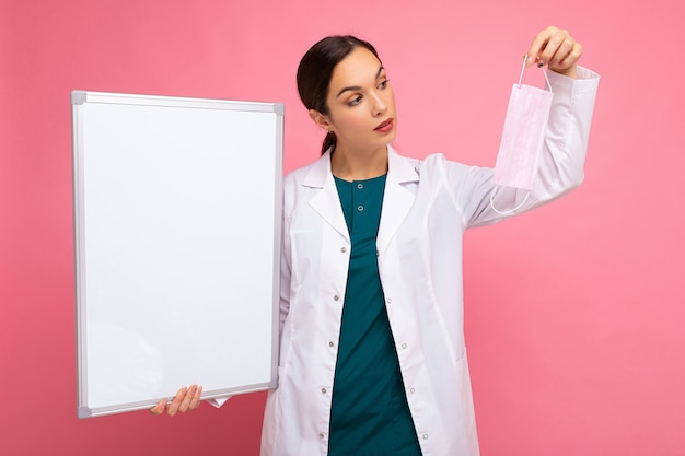 Kobieta lekarz w białym fartuchu medycznym trzymając pustą tablicę z miejscem na tekst i maskę ochronną na białym tle. koncepcja covid.