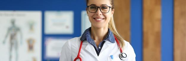 Kobieta lekarz w białym fartuchu stoi w gabinecie lekarskim.