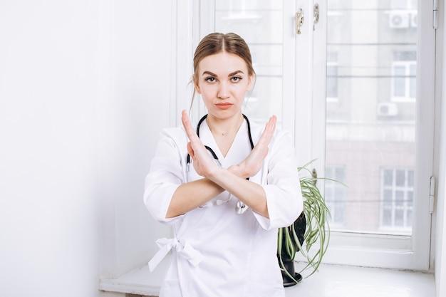 Kobieta lekarz w białym fartuchu ze stetoskopem przeciwko okno w lekkim biurze koncepcja medycyny medycyny apteki i materiałów medycznych