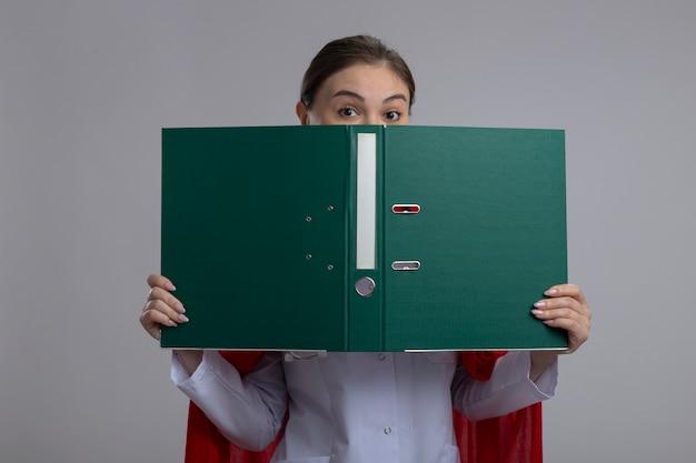 Kobieta lekarz w białym medycznym mundurze i czerwonej pelerynie superbohatera, trzymając otwarty folder przed nią zerkając nad stojącą nad białą ścianą