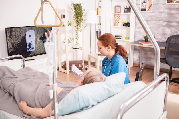 Kobieta lekarz w domu opieki z senior kobietą przed telewizorem.