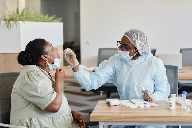 Kobieta lekarz w kombinezonie ochronnym pobiera wymaz z nosa w celu pobrania próbek do laboratoryjnego testu na koronawirusa