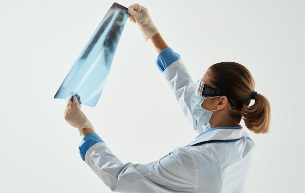 Kobieta lekarz w masce medycznej bada zdjęcie rentgenowskie na jasnym tle.
